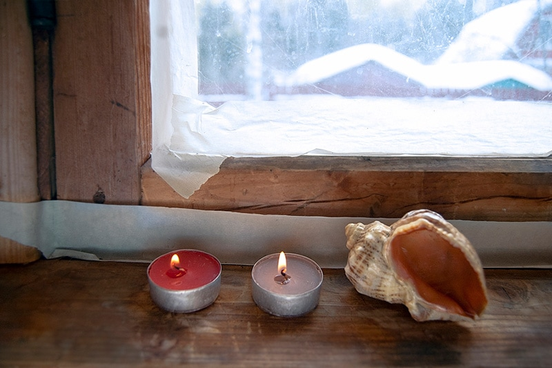 candles lite by a window in winter, How Can I Save Money on My Heating Bill This Winter?